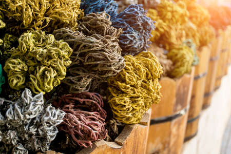 Colored dried seaweed shaped into decorative balls lays in the wooden baskets on the street market