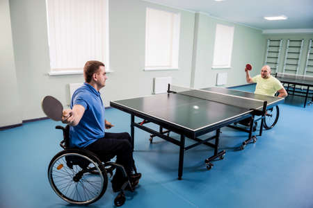 Adult disabled men in a wheelchair playing table tennis Stock Photo