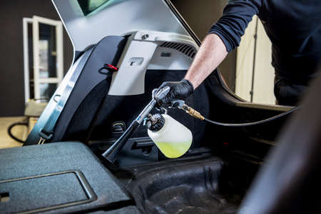 A car service worker cleans interiror with a special foam generator