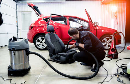Car service worker cleaning car seat with vacuum cleaner.