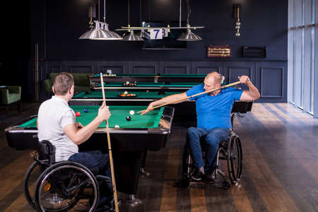Adult men with disabilities in a wheelchair play billiards in the club Standard-Bild