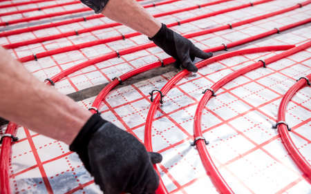 Pipefitter install system of underfloor heating system at home
