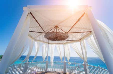 Romantic gazebo on the beach with blue sea
