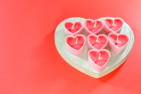 pink candles in the form of a heart on a red background for Valentine's day . High quality photo
