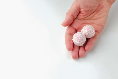 pink chocolate candy in hand on a white background. candy ball macro. isolate Фото со стока