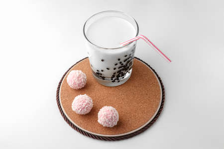 pink chocolate candy and a glass of milk on a white background. candy ball macro. isolate