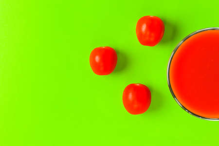 red tomato and a glass of tomato juice on a green background. hard shadow. isolate Фото со стока