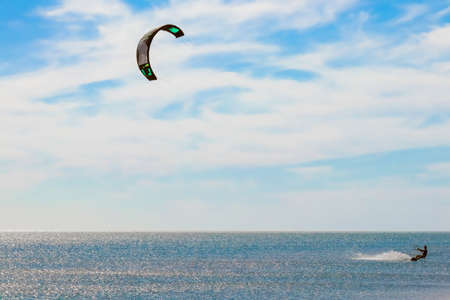 a kitesurfer surfing on the smooth azure water. recreational sport. A Man Rides A Kiteboarding In The Sea Water. extreme sport. Jump