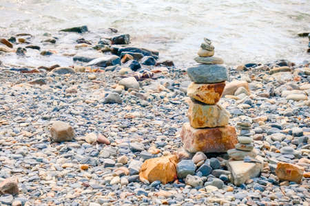pebbles and stones on the beach. waves and splashes on the shore Фото со стока