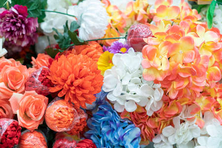 artificial multicolored flowers close up as background
