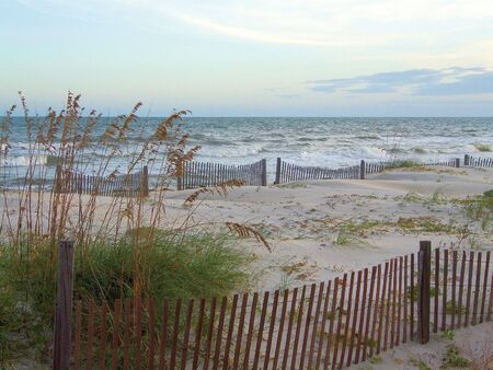 Waves rolling in at St. George Island, Florida. Fences and sea oats line the beach.