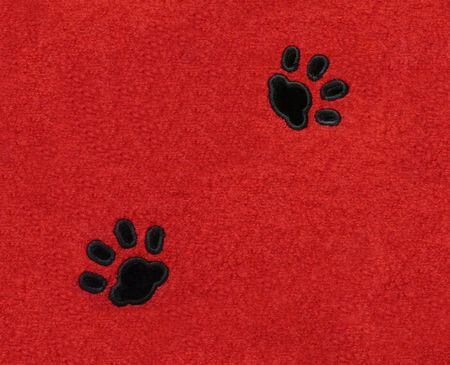 Two black velvet pawprints of a cat on red rectangular fabric.