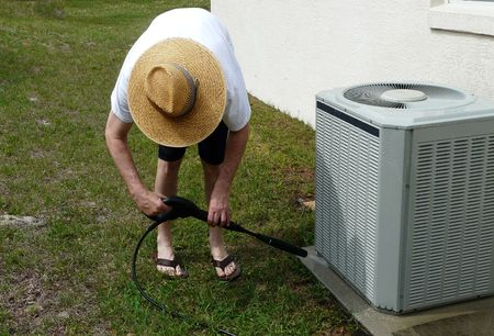conditioner: Male do-it-yourselfer pressure washing the concrete pad of an air conditioning unit. Wearing a straw hat for sun protection. Stock Photo
