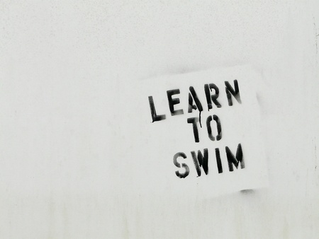 A distressed white sign with the words Learn To Swim in black letters with paint drips, to encourage fitness or to symbolize business metaphors.