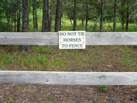 A sign prohibiting tying horses to the fence on a horse camp trail. Stock Photo - 11748617