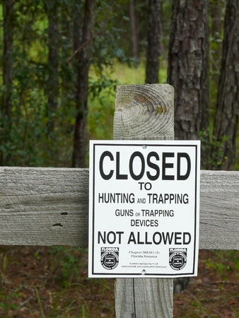 A no hunting or trapping sign on a fence in a state forest. Posted by the Florida Department of Agriculture and Consumer Services, a Division of Forestry.