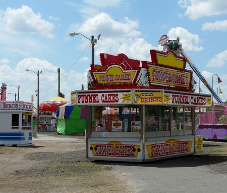 marquees: Concession stand, ticket booth, rides, and games at the county fair on a beautiful day.