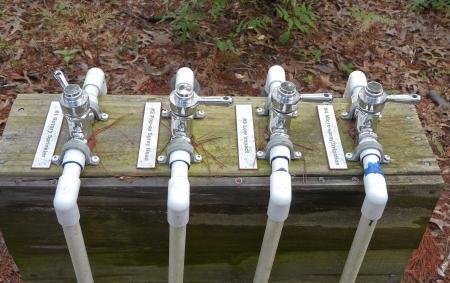 Quatre types de pulvérisateurs et systèmes d'irrigation sont affichées comme une partie du matériel utilisé dans un jardin de démonstration.