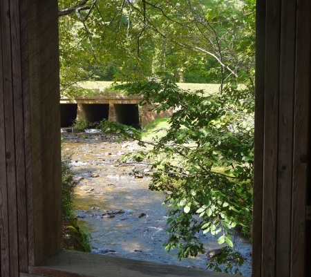 View of a creek from an opening in a wooden foot bridge