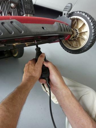 남자는 유선 회전 도구를 사용하여 잔디 깎는 기계에 일으키는 스파크 블레이드를 선명하게됩니다