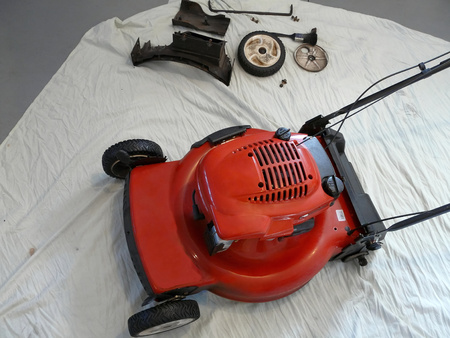 A lawnmower has been partially disassembled for servicing prior to the mowing season