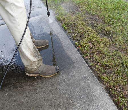 Male do-it-yourselfer pressure washing the sidewalk in front of his house. Banco de Imagens