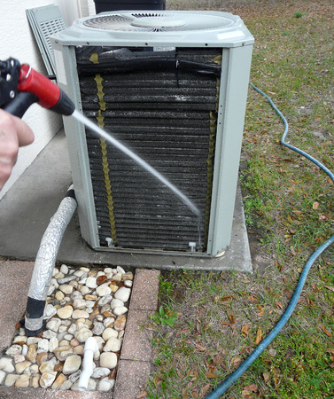 and the air: Man spraying insect repellant on evaporator coils to prevent nesting and feeding ants from damaging the contactor of air conditioner heat pump unit.