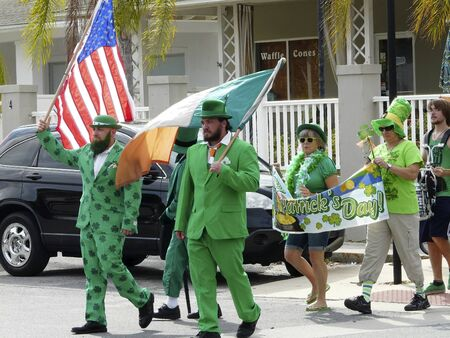 Marchers dressed in green and shamrocks carry flags and a banner in a parade to celebrate Saint Patrick's Day in Crystal River, Florida. Editorial