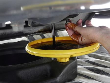 기름을 변경하는 동안 남자 제거 볼트 후 용기에 배출 오일의 확대합니다. 오래된 이불은 드립을 잡을 차고 층에 있습니다. 스톡 콘텐츠