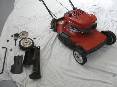A lawn mower has been partially disassembled for servicing prior to the mowing season.
