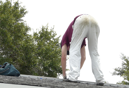A homeowner is on the roof of his residence to fix a leak at the ridge vent. He has on dirty work clothes, and a satchel with supplies is nearby.