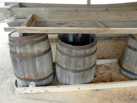 A still at St. Andrews State Park, Panama City, Florida, displays the barrels used to separate turpentine from water when distilling resin from pines. Stock Photo