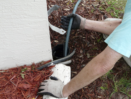 Huiseigenaar maakt gebruik van riool slang of stang aan een verstopping van vuil en bladeren in de PVC pijp duidelijk uit naar een punt waar water kan worden verspreid.