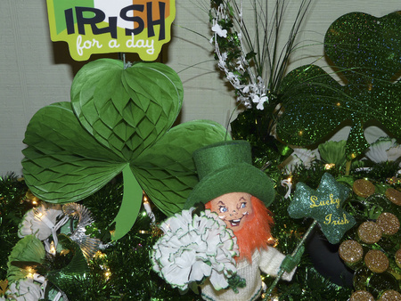 Lighted Saint Patricks Day decorations feature green shamrocks, garland, carnations, gold coins, a leprechaun with a top hat, and Irish signs.