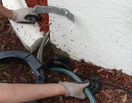 Homeowner uses an encased sewer snake or rod to clear a blockage of dirt and leaves in the PVC pipe out to a point where water can be dispersed.