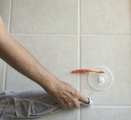 Male homeowner uses paintbrush and grout color/sealer to paint tile grout lines in the kitchen of his residence to repel oils and prevent stains.