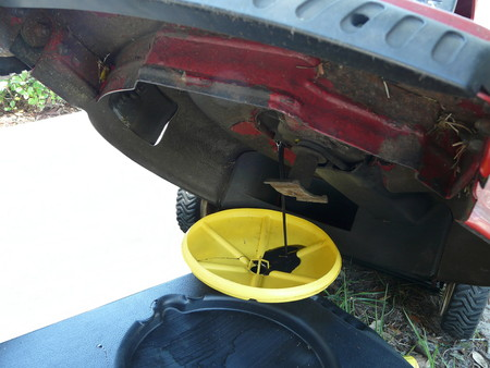 Close-up van olie die in een gele en zwarte container aftappen tijdens een olieverversing op een rode grasmaaimachine.