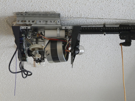 Close-up of an automatic garage door opener motor gear drive needing repair at a residence. Stock Photo