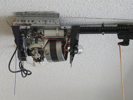 Gros plan d'un générateur d'engrenage à moteur automatique d'ouvre-porte de garage nécessitant une réparation dans une résidence. Banque d'images
