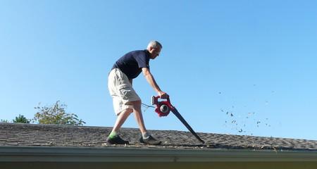 Un propietario está en el techo de su residencia usando un soplador de hojas para quitar las hojas de la canaleta en preparación para la escorrentía de agua de la temporada de tormentas.