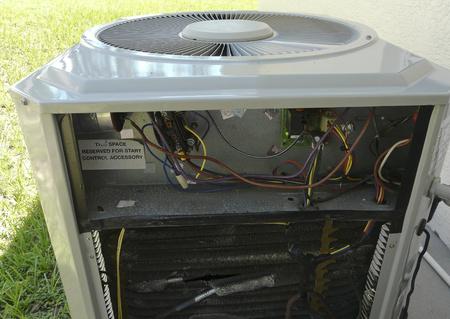 Condizionatore d'aria residenziale e unità a pompa di calore con un lato del case rimosso per la riparazione, esponendo il pannello di controllo elettronico e le batterie dell'evaporatore.