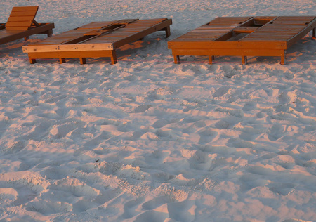 The sun setting on beach chairs for rent at Panama City Beach, Florida, gives the sand a pink tinge.