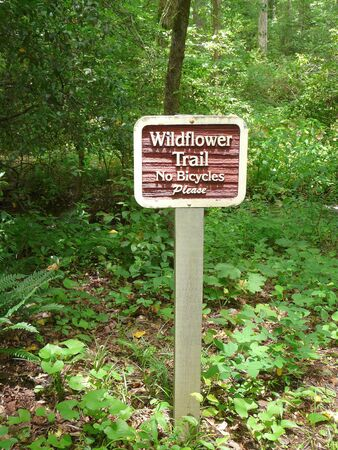 PINE MOUNTAIN, GEORGIA-JUNE 5, 2018: This Callaway Gardens sign prohibits bicycles on a trail to protect native plants in affiliation with the Lady Bird Johnson Wildflower Center in Austin, Texas.