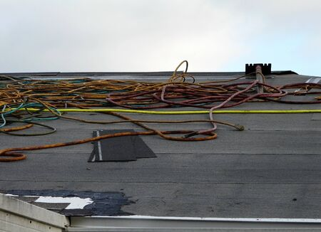 A secondary water resistance underlayment of polymer has been installed during a roof replacement. Electrical cords and shingle scraper are visible. 写真素材