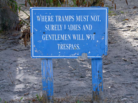 This worn posted sign on personal property in the South warns against trespassing in a humorous, polite manner.