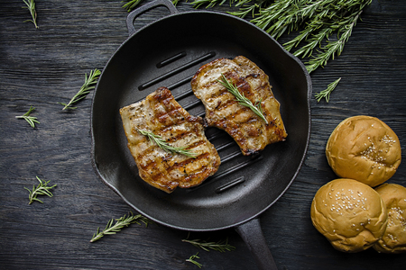 Grilled steak on a round grill pan, decorated with spices for meat, rosemary on a dark wooden background. View from above.