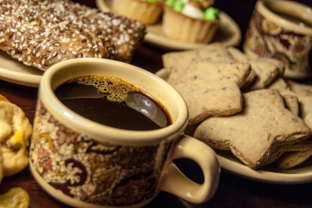 A cup of coffee and cookies on a table
