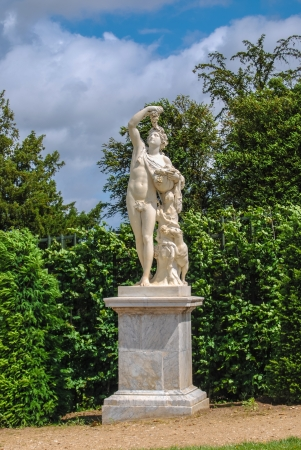 statue of Bacchus with grape in the Gardens of Versailles, France photo