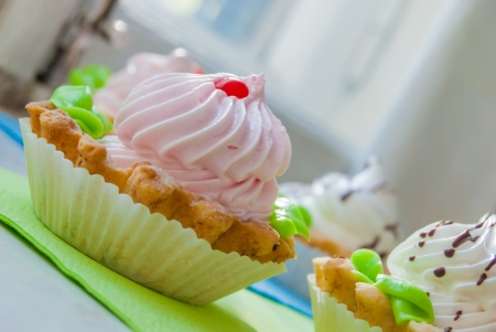 colored cupcakes on napkins in morning sunlight near window, macro photo