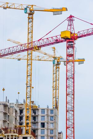 colored cranes and a building on a construction site photo